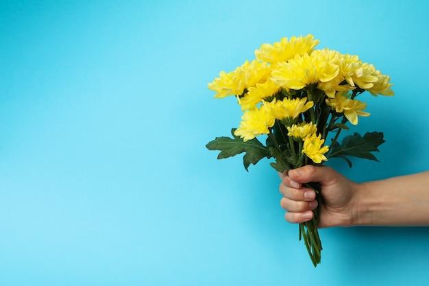 Weibliche hand hält chrysanthemenstrauß