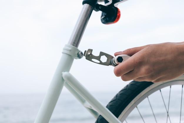 Weibliche hand hält das werkzeug, um fahrrad zu reparieren