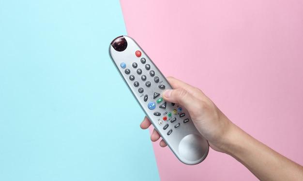 Weibliche hand hält die tv-fernbedienung auf rosa blau pastell. draufsicht