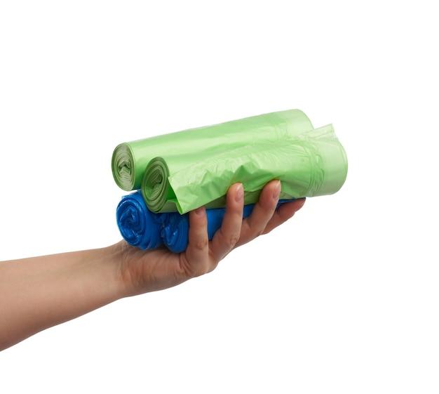Weibliche hand hält ein bündel von blauen und grünen plastiktüten für müll