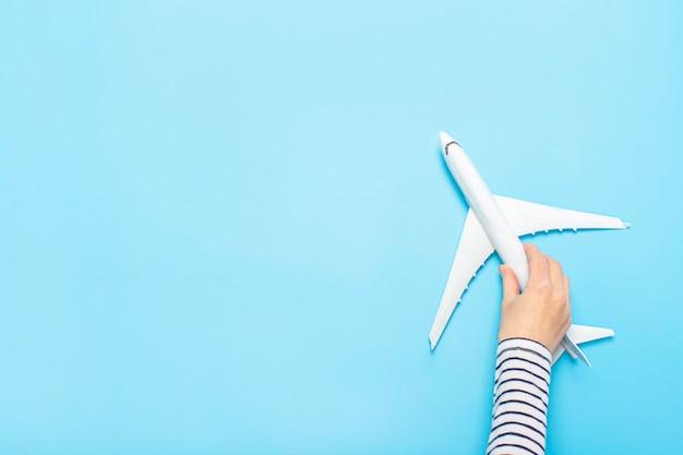 Weibliche hand hält ein flugzeug auf einem blau. konzeptflug, tickets, buchung, flugsuche, reisen.