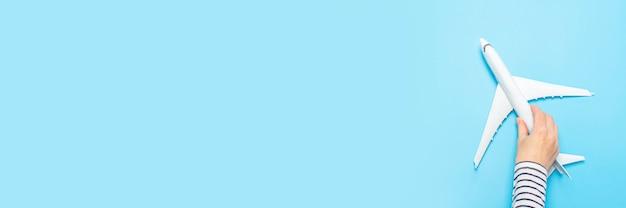 Weibliche hand hält ein flugzeug auf einem blauen raum. konzeptflug, tickets, buchung, flugsuche, reisen. banner