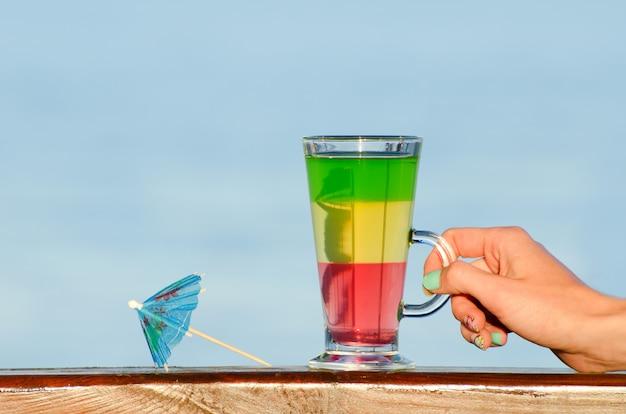 Weibliche hand hält ein glas mit buntem cocktail an der wand des meeres, regenschirm für cocktails