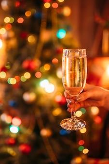 Weibliche hand hält ein glas mit champagner, weihnachtstradition, romantische feier.