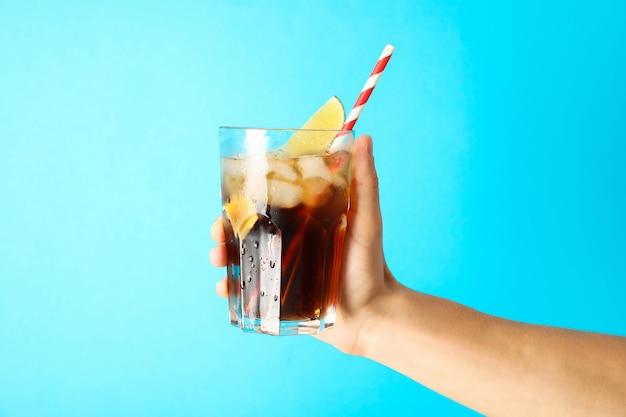 Weibliche hand hält ein glas mit eis cola, tubulus und limettenscheibe