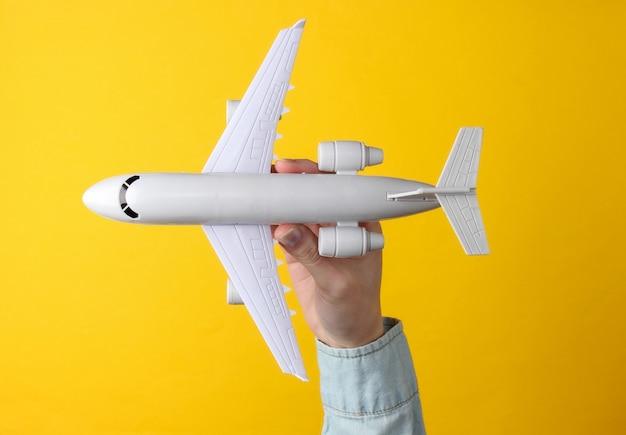 Weibliche hand hält ein spielzeugflugzeug auf einem gelben. reisekonzept