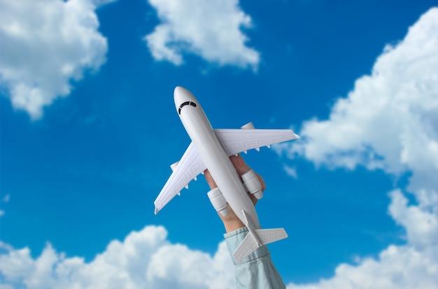 Weibliche hand hält ein spielzeugflugzeug gegen den blauen himmel mit weißen wolken. reisekonzept