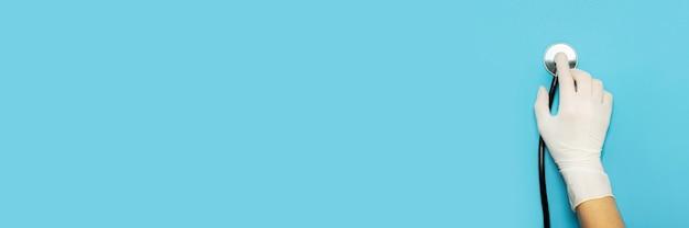 Weibliche hand hält ein stethoskop auf einem blau. konzept arztbesuch, virus, behandlung, diagnose.