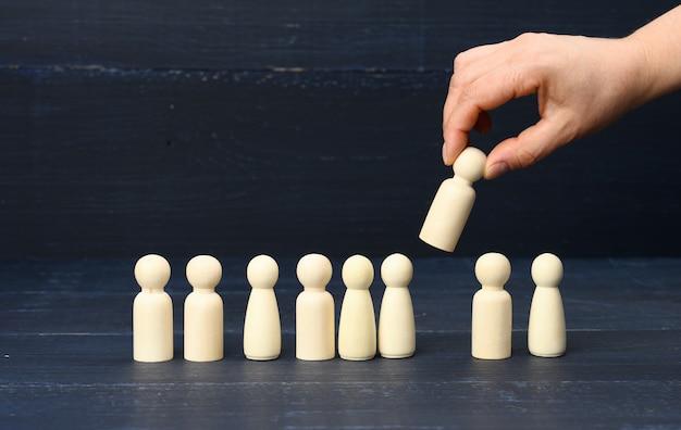 Weibliche hand hält eine aus der menge ausgewählte holzfigur. das konzept, talentierte mitarbeiter, manager, karrierewachstum zu finden. personaleinstellung