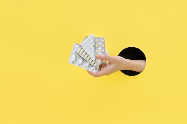 Weibliche hand hält eine blase mit pillen auf einem gelben hintergrund