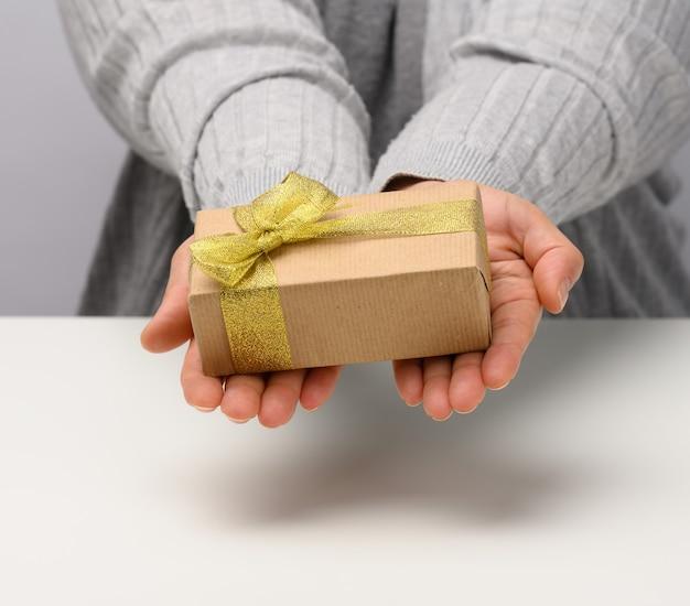 Weibliche hand hält eine geschenkbox auf grauem hintergrund, alles gute zum geburtstagskonzept, nahaufnahme
