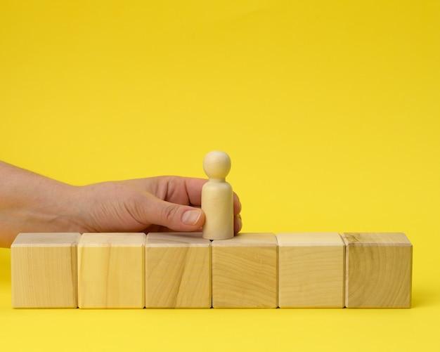 Weibliche hand hält eine holzfigur eines mannes und setzt einen würfel auf. förderkonzept, coaching und mentoring