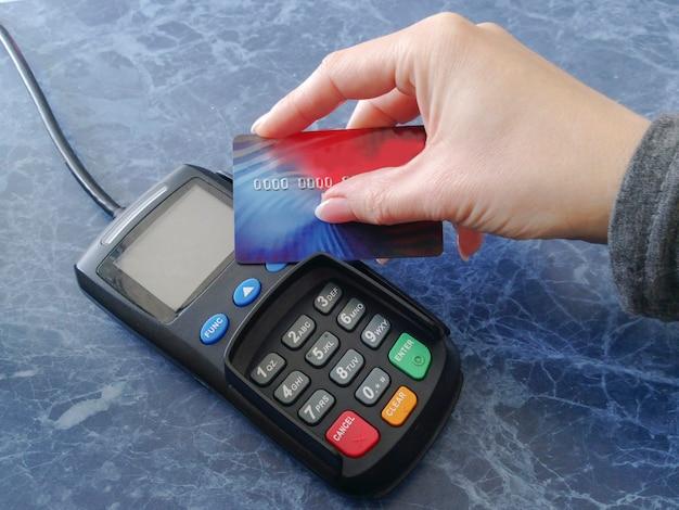 Weibliche hand hält eine kreditkarte auf dem zahlungsterminal. kassierer zum abheben von geld. nfc-technologie. finanzen und bargeldlose zahlungsweise.