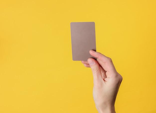 Weibliche hand hält eine leere braune visitenkarte