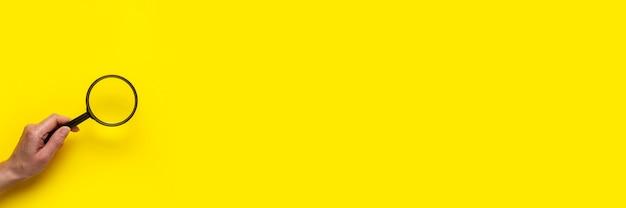 Weibliche hand hält eine lupe auf einer gelben oberfläche. banner.