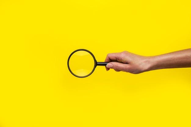 Weibliche hand hält eine lupe auf einer gelben oberfläche.