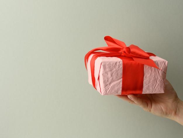 Weibliche hand hält eine rosa geschenkbox auf grauem hintergrund, alles gute zum geburtstag konzept