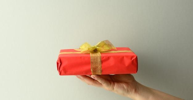 Weibliche hand hält eine rote geschenkbox auf grauem hintergrund, alles gute zum geburtstag konzept