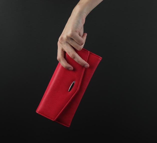 Weibliche hand hält eine rote lederhandtasche auf einem schwarzen hintergrund