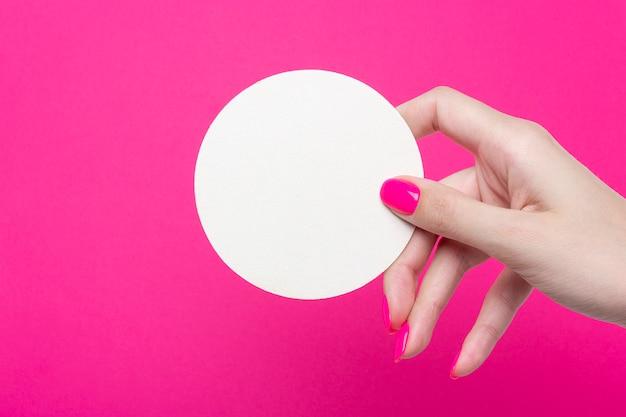 Weibliche hand hält eine runde leere untersetzer auf rosa hintergrund