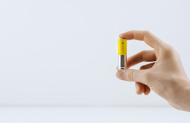 Weibliche hand hält eine salzbatterie lokalisiert auf weißem hintergrund, kopienraum
