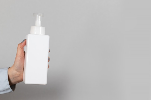 Weibliche hand hält eine weiße plastikflasche mit antibakteriellem seifendesinfektionsmittel auf einem grauen hintergrund. coronavirus und pandemieschutzmittel.