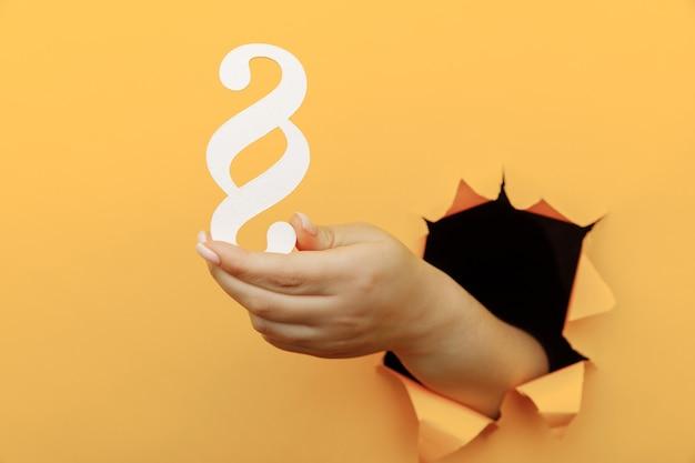 Weibliche hand hält einen absatz als zeichengesetz durch.