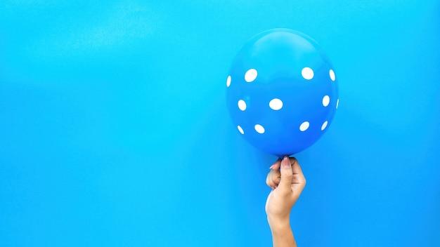 Weibliche hand hält einen ballon mit weißen kreisen