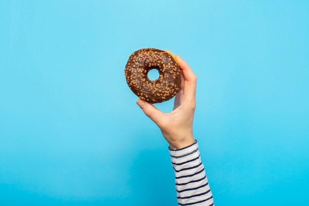 Weibliche hand hält einen donut auf einem blauen raum. konzept süßwarenladen, gebäck, café. banner. flache lage, draufsicht