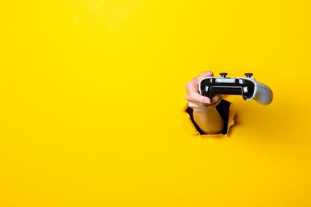 Weibliche hand hält einen joystick auf einem hellen gelben hintergrund