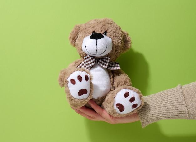 Weibliche hand hält einen kleinen braunen spielzeug-teddybär auf grünem hintergrund