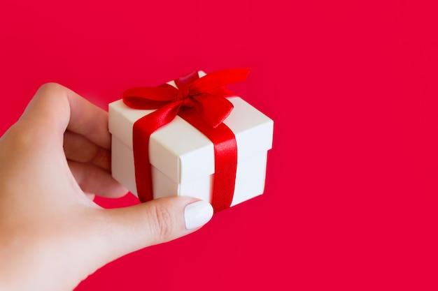 Weibliche hand hält einen kleinen weißen kasten mit einem roten bogen auf einem rot. geschenk in einer weiblichen hand, kopienraum