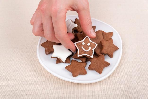 Weibliche hand hält einen lebkuchenplätzchen in form des sternemoticons. glasierte gemalte kekse.
