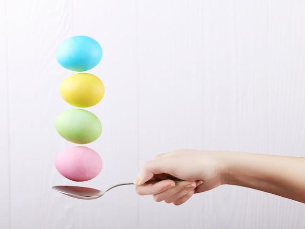 Weibliche hand hält einen löffel, auf dem mehrfarbige eier, auf einem weißen hintergrund balanciert werden. ungewöhnliches design, ostern-konzept, kopienraum.