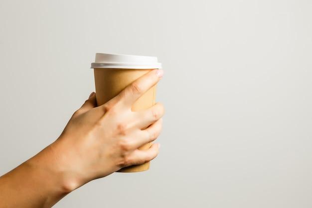 Weibliche hand hält einen pappbecher mit kaffee auf grauem hintergrund. konzept von kaffee, einem wärmenden getränk, frühstück.