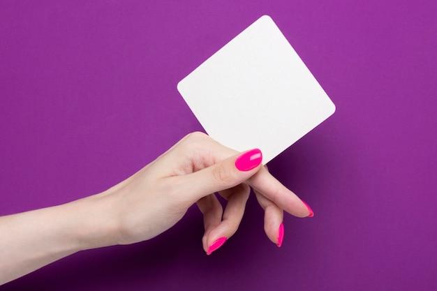 Weibliche hand hält einen quadratischen untersetzer auf einem lila hintergrund.