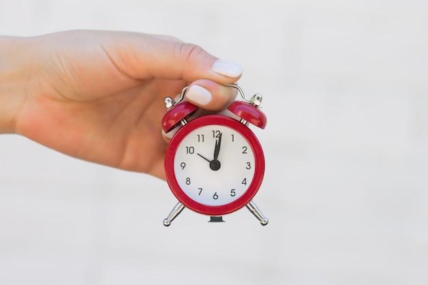 Weibliche hand hält einen roten wecker auf der ausgestreckten hand. zeit, schlaf, erweckungskonzept
