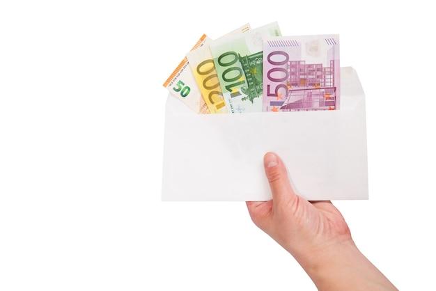 Weibliche hand hält einen umschlag mit euro auf einer weißen oberfläche. speicherplatz kopieren.