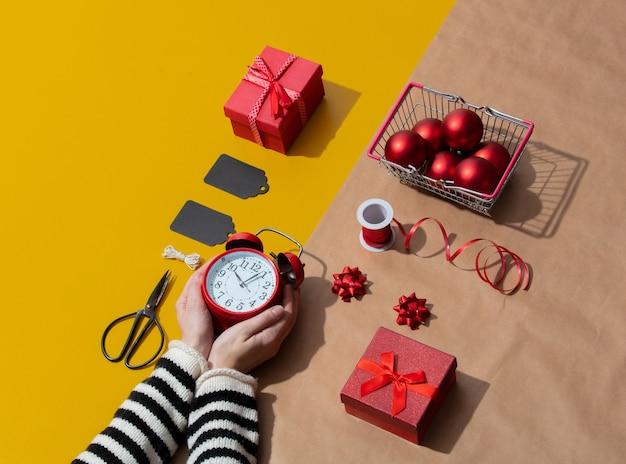 Weibliche hand hält einen wecker in der nähe von weihnachtsgeschenken