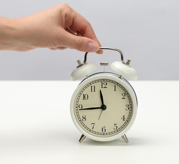 Weibliche hand hält einen weißen metallwecker auf einem weißen tisch, die zeit ist fünfzehn vor zwölf. konzept der abgabefrist für die aufgabe