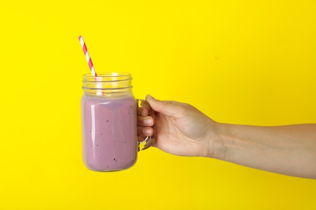 Weibliche hand hält glas smoothie auf gelbem hintergrund