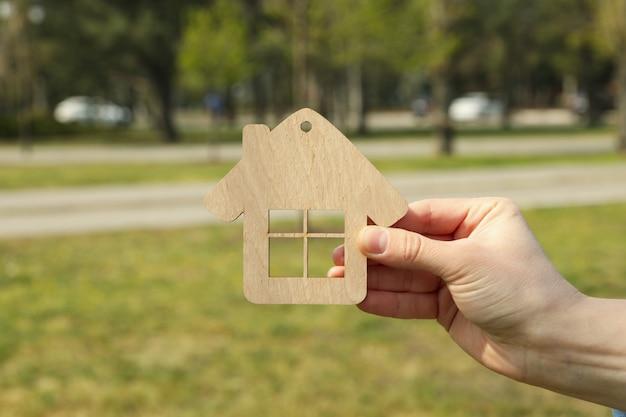 Weibliche hand hält holzhaus. eine immobilie kaufen