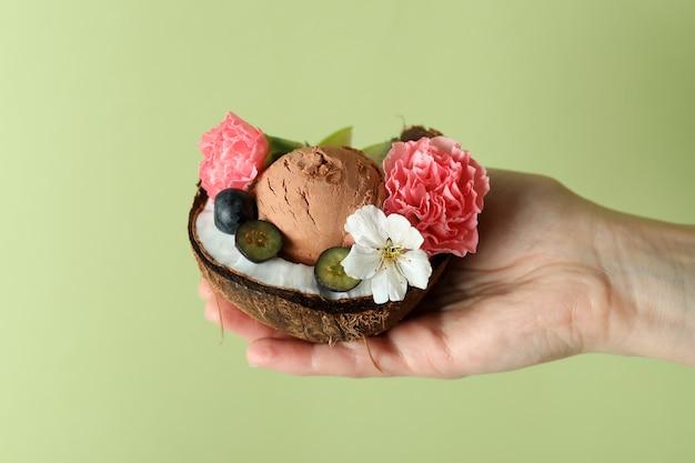 Weibliche hand hält kokosnuss mit fruchteis auf grünem hintergrund
