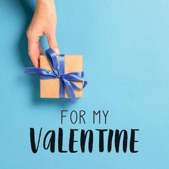 Weibliche hand hält, nimmt, erhält ein geschenk auf einer blauen oberfläche