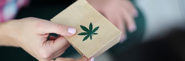 Weibliche hand hält papiertüte mit einem bild der marihuana-symbol-nahaufnahme. online-lieferung von marihuana-produktkonzept