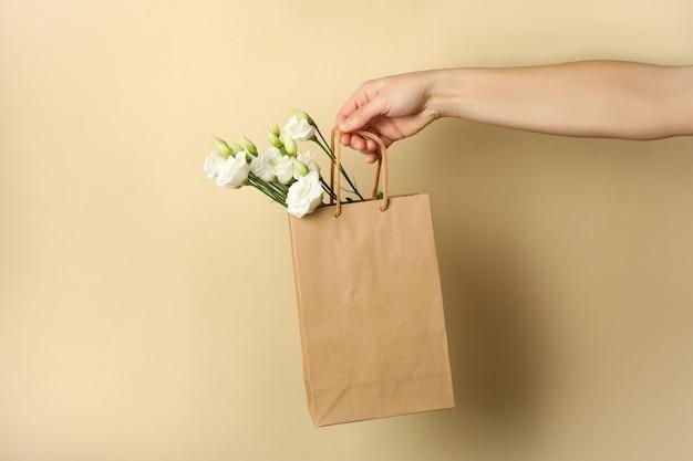 Weibliche hand hält papiertüte mit rosen auf beigem hintergrund