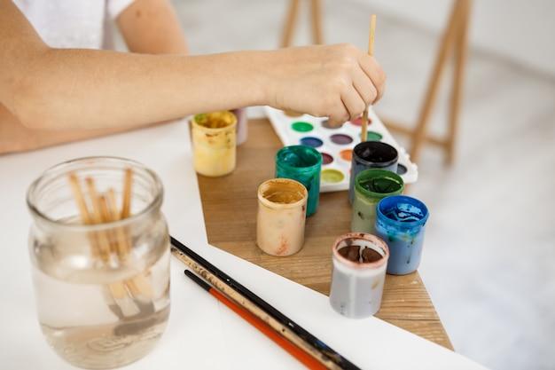 Weibliche hand hält pinsel und vertieft ihn in farbe. kindermalerei unter verwendung von aquarell während des unterrichts im kunstraum.