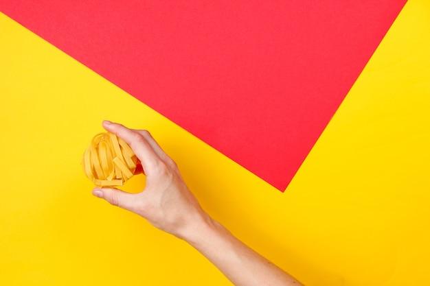 Weibliche hand hält rohe tagliatelle-nudeln auf farbigen. minimalistisches lebensmittelkonzept. draufsicht