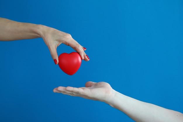 Weibliche hand hält rotes herz und überträgt es auf männliche hand.