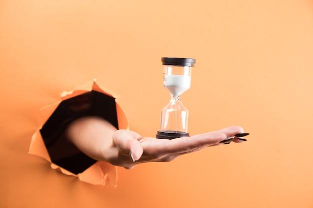 Weibliche hand hält sanduhr auf orangem hintergrund